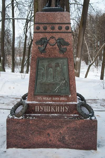 На лицевой грани пьедестала - бронзовый барельеф с изображением А.С. Пушкина, сидящего в овальном зале остафьевского дома.
